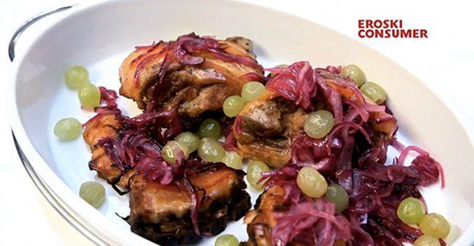 Cochinillo tostado con guarnición de cebolla morada y uvas moscatel